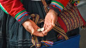 Close up of weaving and culture in Peru. Cusco, Peru: woman dressed in colorful traditional native Peruvian closing holding stock photography