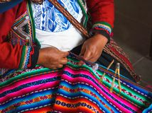 Close up of weaving in Peru. Cusco, Peru. Woman dressed in colorful traditional native Peruvian closing knitting a carpet with stock images