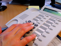 Hands and phone. Beautiful female hand on the office phone royalty free stock images