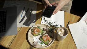 Hands with the phone close-up pictures of food. Breakfast for two : sandwich, coffee, toast. stock video footage