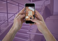 Hands with phone showing desk against stairs with purple overlay Stock Photography