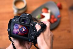 Hands of photographer holding dslr camera taking a photo of a strawberry dessert royalty free stock photography