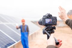 Hands of the photographer show a gesture, photographing a solar battery worker on camera. Outdoors. royalty free stock image