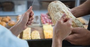 Hands photographing bread through transparent device. Digital composite of Hands photographing bread through transparent device Stock Image