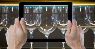 Hands photographing wine glasses through digital tablet at bar Stock Photos