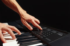 Hands of pianist play the keys of the electronic synthesizer on black background Stock Image