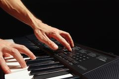 Hands of pianist play the keys of the synth on black background Royalty Free Stock Photos