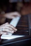 Hands on piano. Hands on a piano keyboard royalty free stock photos