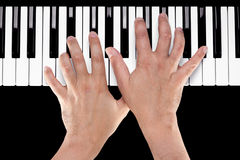 Hands on a Piano Keyboard. Hands playing a chord of Ab major over C bass on a piano keyboard shot from above with a black background royalty free stock photos