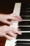 Hands on the piano keyboard (blurred). The hands of a young musician who's playing the piano Royalty Free Stock Images