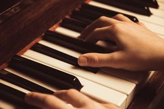 The hands on the piano keys. Photo piano in retro style.  Stock Photo