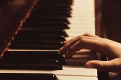 The hands on the piano keys. Photo piano in retro style.  Royalty Free Stock Photos