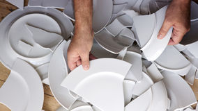 Hands picking up broken white plates of floor. Hands picking up broken white plates from wooden floor royalty free stock photography