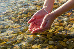 Hands picking up water Stock Photography