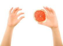 Hands with piece of grapefruit and capsules Royalty Free Stock Image