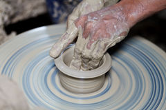 Hands on a piece of pottery made of clay Stock Image