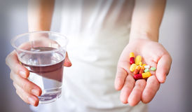 Hands with pills and glass of water isolated on white Stock Images