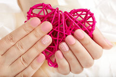 Hands with pink matte manicured nails holding a heart Stock Images