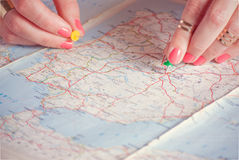 Hands pinning travel destination points on map, filtered Royalty Free Stock Photo
