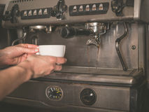 Hands placing cup under coffee machine Stock Images