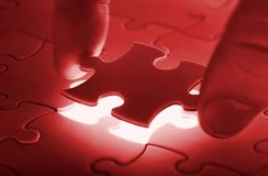 Hands placing last piece of a Puzzle. Close up stock photos