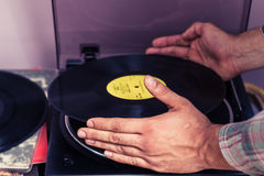 Hands placing LP on turntable Royalty Free Stock Image