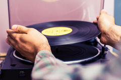 Hands placing record on turntable Royalty Free Stock Photo