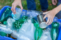 Hands placing recycling items in recycling bin Royalty Free Stock Photography