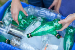 Hands placing recycling items in recycling bin Royalty Free Stock Images