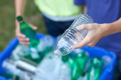 Hands placing recycling items in recycling bin Stock Images