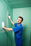 Hands plasterer at work. Application of the plaster on the wall. Portrait of young pretty man on construction site: male worker plastering walls with spatula Royalty Free Stock Image