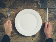 Hands with plate, knife and fork Stock Photos