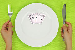 Hands and plate with weighing scale Stock Image