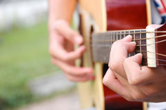Hands play guitar Stock Image