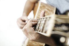 Hands playing an acoustic guitar Stock Images