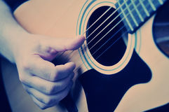 Hands playing acoustic guitar Stock Images