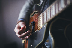 Hands playing electric guitar Stock Images
