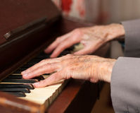 Hands playing a harmonium. Elderly hands playing on an old harmonium Stock Images