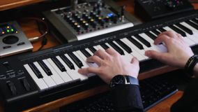 Hands playing midi electronic piano while composing pop rock hit song in home recording music studio with mixing board and soundbo. Ard. Professional music stock footage