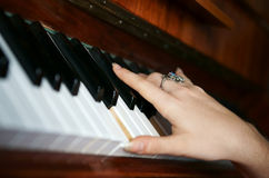 Hands playing music on the piano Stock Images