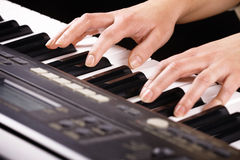 Hands playing music on the piano Stock Image