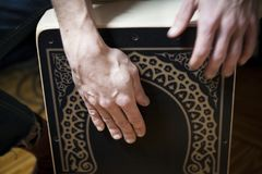 Hands playing percussion with a Flamenco box. White man detail shot hands playing percussion with a Flamenco box sitting on top of it on a home environment stock photo