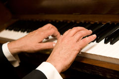 Hands playing piano. A man's hands playing the piano royalty free stock image