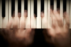 Hands playing piano Stock Images