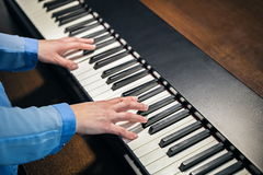 Hands playing the piano Stock Photos