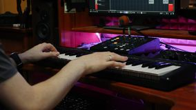 Hands playing on piano midi keyboard in music studio. Pop composer creating new song for music album. Home music recording studio