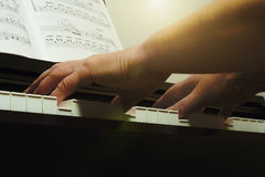 An elderly woman playing the piano warm light. Hands playing the piano. Warm light, contrast image closeup Royalty Free Stock Photo