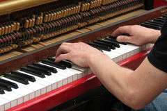 Hands playing upright piano Stock Image