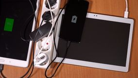 Hands plug tablet computers and phones to chargers in extension sockets. Hands plug tablet computers and phones to chargers in extension cord sockets on wooden stock footage