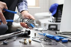 Hands plumber at work in a bathroom, plumbing repair service, as royalty free stock photo